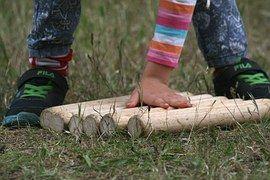 child lining up logs