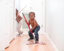 young boy sweeping hallway