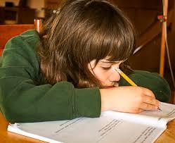 girl leaningn over book doing homework