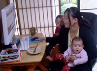 mom with two children on lap trying to work